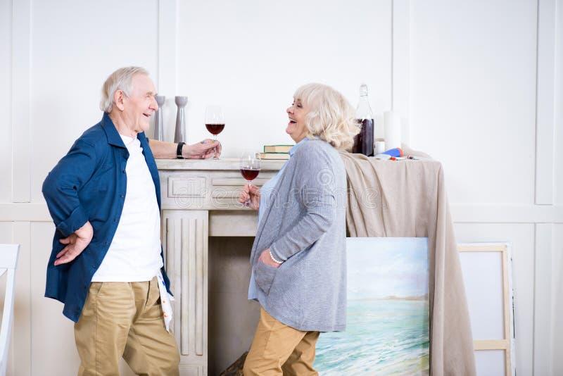 Vino de consumición sonriente de los pares mayores en taller del arte imagenes de archivo