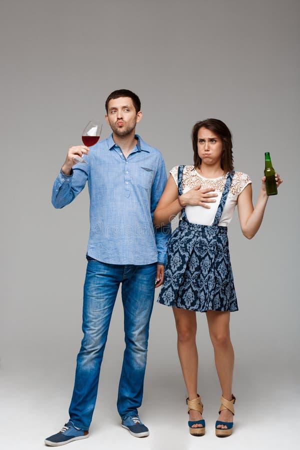 Vino de consumición y cerveza de los pares hermosos jovenes sobre fondo gris fotos de archivo