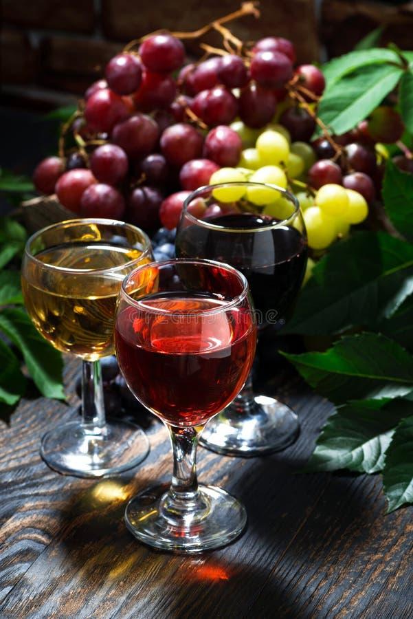vino differente dell'assortimento su fondo di legno scuro, verticale immagini stock