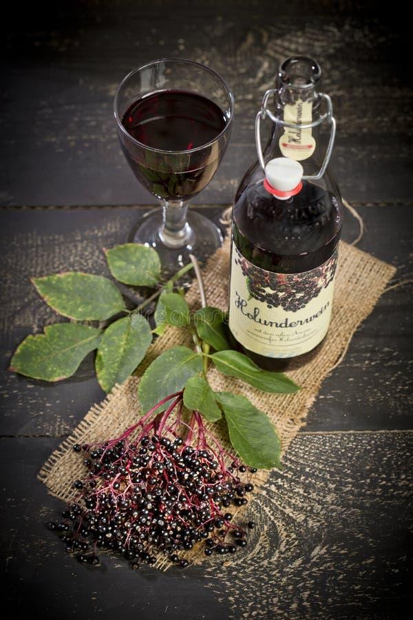 Vino e bacche di sambuco della bacca di sambuco sulla tavola di legno fotografia stock