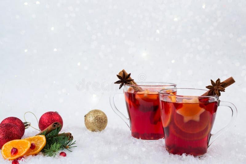 Vino e ingredientes reflexionados sobre la Navidad En el fondo blanco de la nieve fotografía de archivo libre de regalías