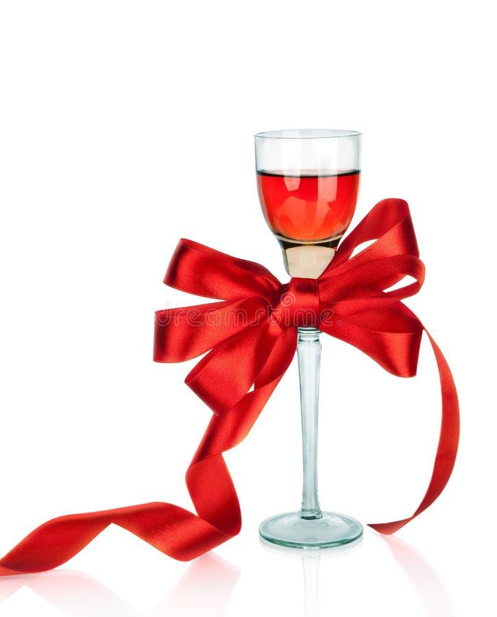 Vino en copa y arqueamiento rojo del regalo del satén,   fotografía de archivo libre de regalías
