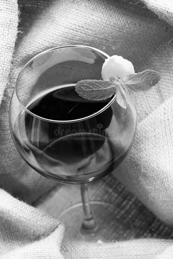 Vino fresco en vidrio con la decoración Hojas y jengibre de menta sobre el vidrio Sommelier y degustación de vinos foto de archivo libre de regalías