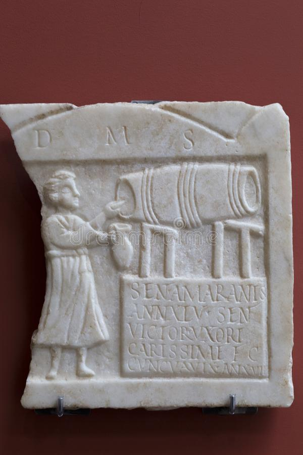 Vino que golpea ligeramente de un barril, Roman Relief del encargado de la taberna foto de archivo