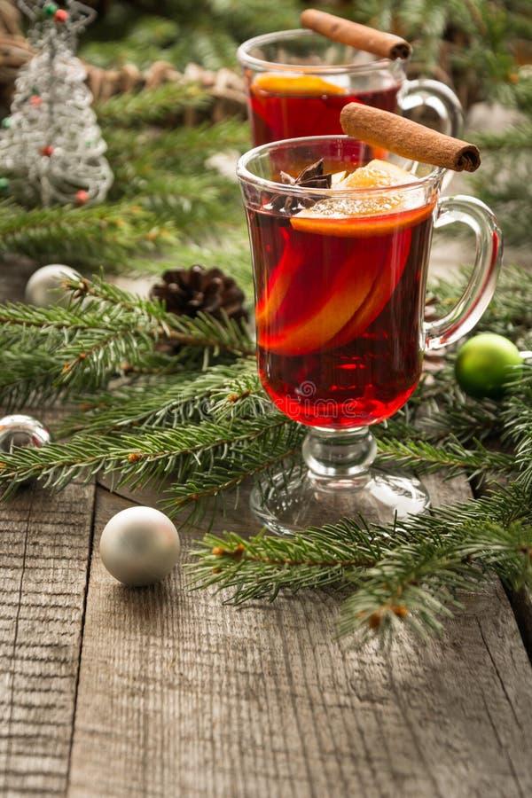 Vino reflexionado sobre caliente de la Navidad con canela, la naranja y el árbol de navidad a bordo Bebida de la tradición del in foto de archivo