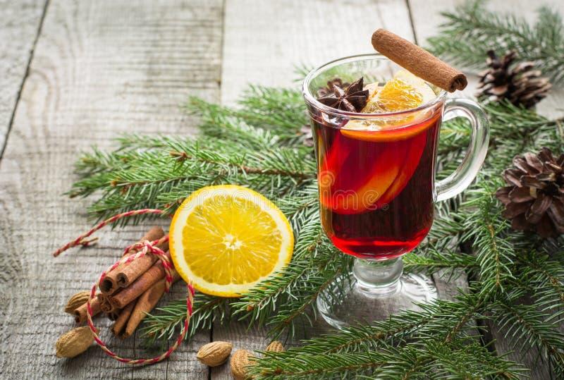Vino reflexionado sobre caliente de la Navidad con canela, la naranja y el árbol de navidad en el tablero de madera Bebida de la  foto de archivo libre de regalías