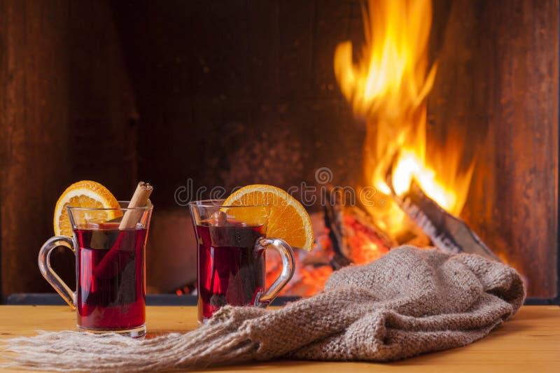 Vino reflexionado sobre en la luz de un fuego acogedora de la chimenea solamente imagen de archivo libre de regalías