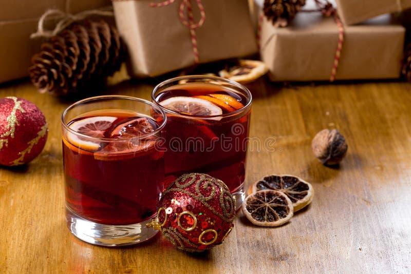 Vino reflexionado sobre en la taza de cristal con las especias Bebida caliente de la Navidad en la tabla de madera con los presen fotos de archivo libres de regalías