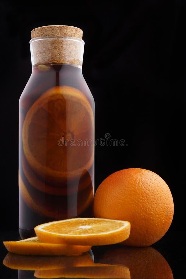 Vino reflexionado sobre en una botella con un corcho al lado de una naranja en un fondo negro imagenes de archivo