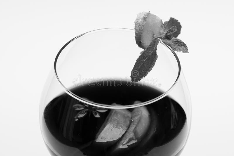 Vino reflexionado sobre en vidrio con la decoración Raíz del jengibre, anís, rebanadas de la manzana y hojas de menta sobre el vi imagen de archivo