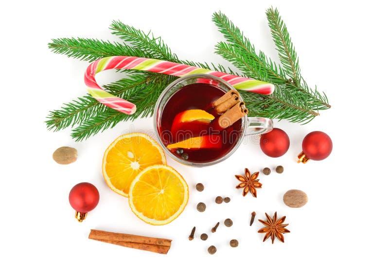 Vino reflexionado sobre rojo caliente aislado en el fondo blanco con las especias de la Navidad, los palillos anaranjados de la r foto de archivo