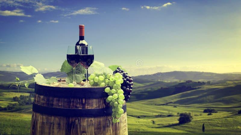 Vino rojo con barril en los viñedos de Chianti, Toscana, Italia foto de archivo
