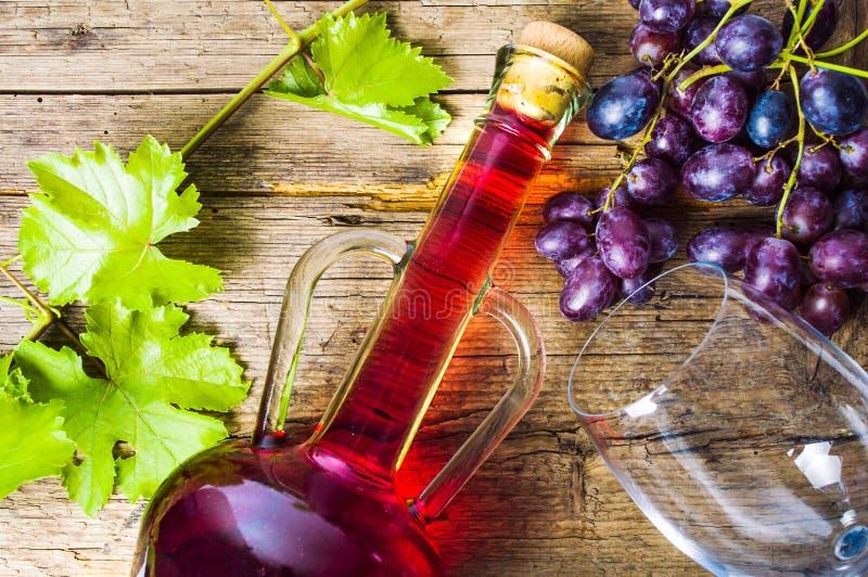 Vino rojo con la uva en fondo de madera rústico imagen de archivo