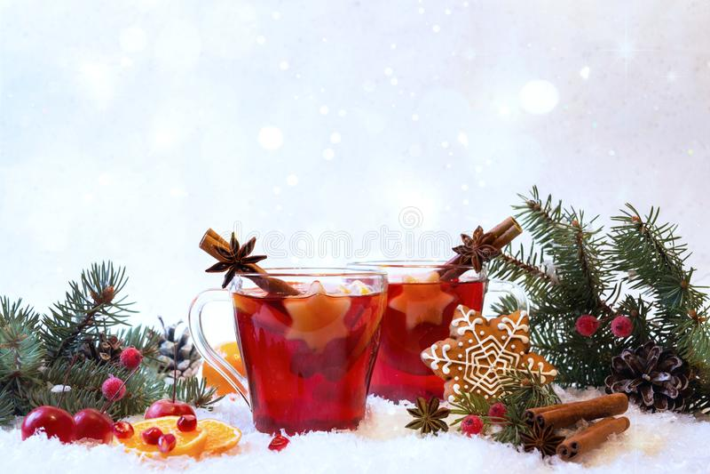 Vino rojo condimentado reflexionado sobre caliente en la taza de cristal con con las luces y el pan de jengibre festivos de la de fotografía de archivo libre de regalías