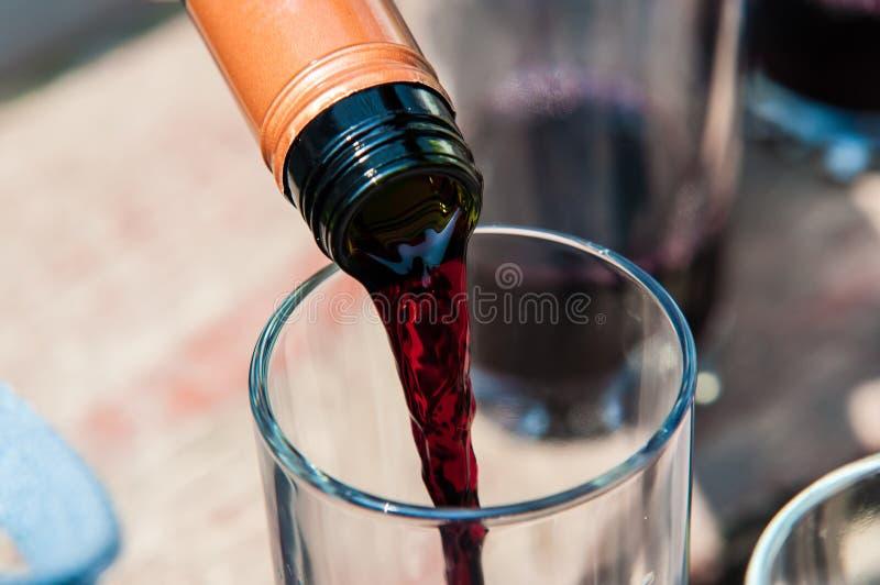 Vino rojo de colada en el vidrio fotos de archivo libres de regalías