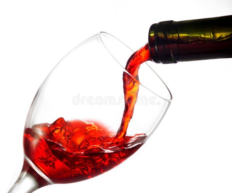 Vino rojo de colada en el vidrio de vino foto de archivo libre de regalías