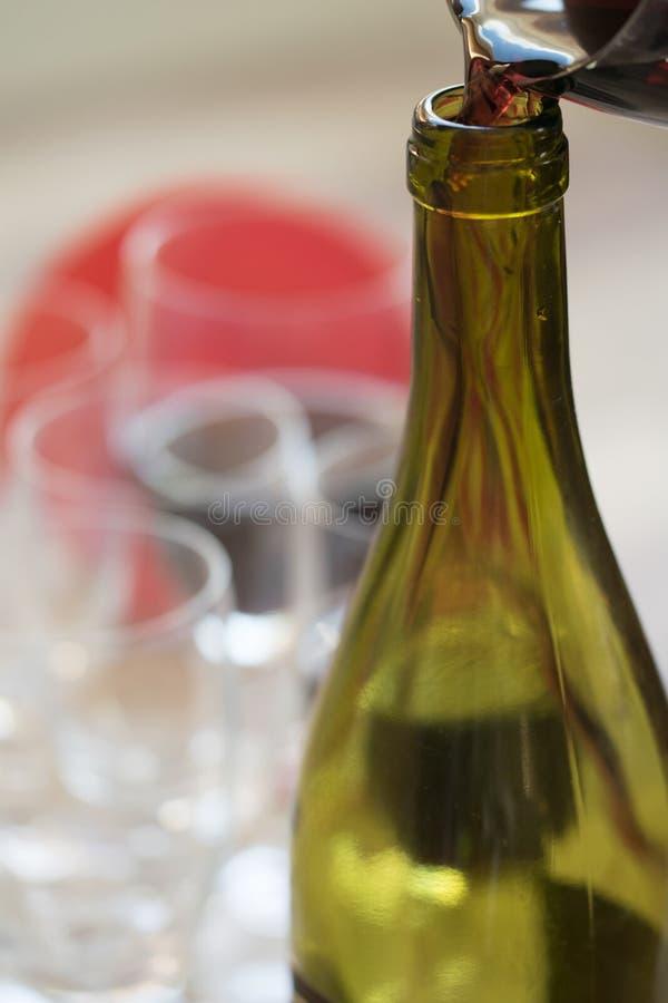 Vino rojo de colada en una botella foto de archivo