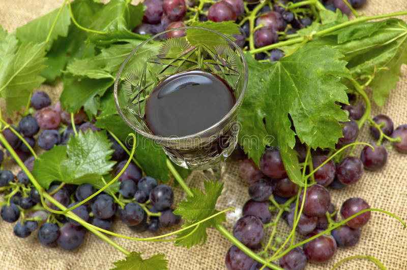 Vino rojo en copa de vino con las uvas dulces. foto de archivo