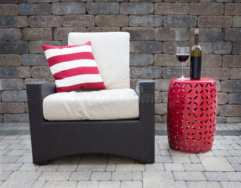 Vino rojo en la tabla al lado de la silla en patio exclusivo foto de archivo libre de regalías