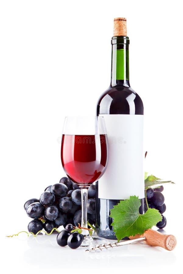 Vino rojo en vidrio con las uvas fotos de archivo libres de regalías