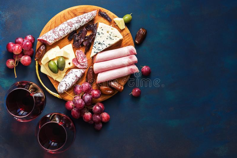 Vino rojo en vidrios, aperitivo, uvas, carne fría, queso con moho Bocados de la charcutería en un fondo azul Visión superior, SP  fotos de archivo libres de regalías