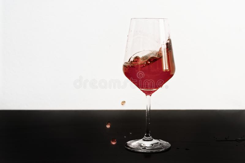 Vino rojo que salpica fuera de un vidrio imagen de archivo libre de regalías