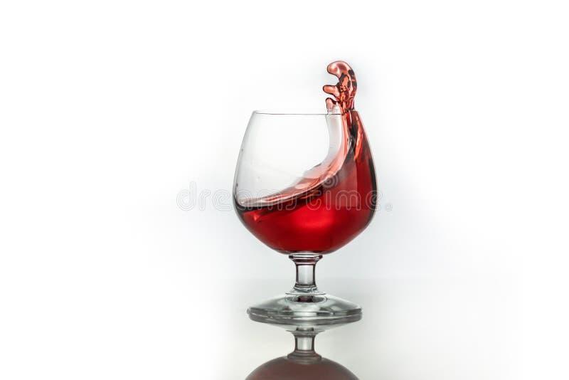 Vino rojo que salpica fuera de un vidrio, aislado en blanco foto de archivo
