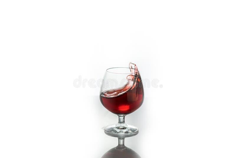 Vino rojo que salpica fuera de un vidrio, aislado en blanco imagen de archivo