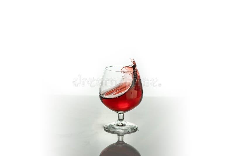 Vino rojo que salpica fuera de un vidrio, aislado en blanco fotos de archivo