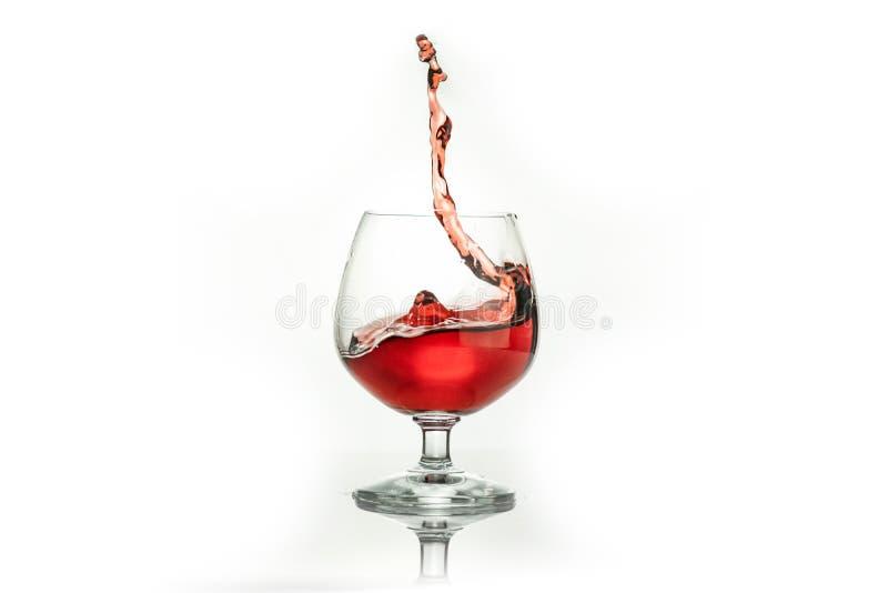 Vino rojo que salpica fuera de un vidrio, aislado en blanco imagenes de archivo