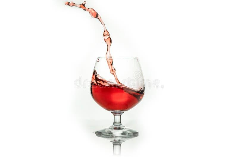 Vino rojo que salpica fuera de un vidrio, aislado en blanco fotografía de archivo