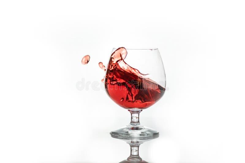 Vino rojo que salpica fuera de un vidrio, aislado en blanco foto de archivo libre de regalías