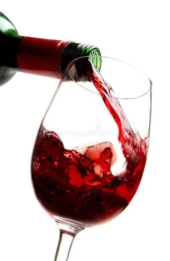 Vino rojo que vierte en el vidrio de vino fotos de archivo libres de regalías