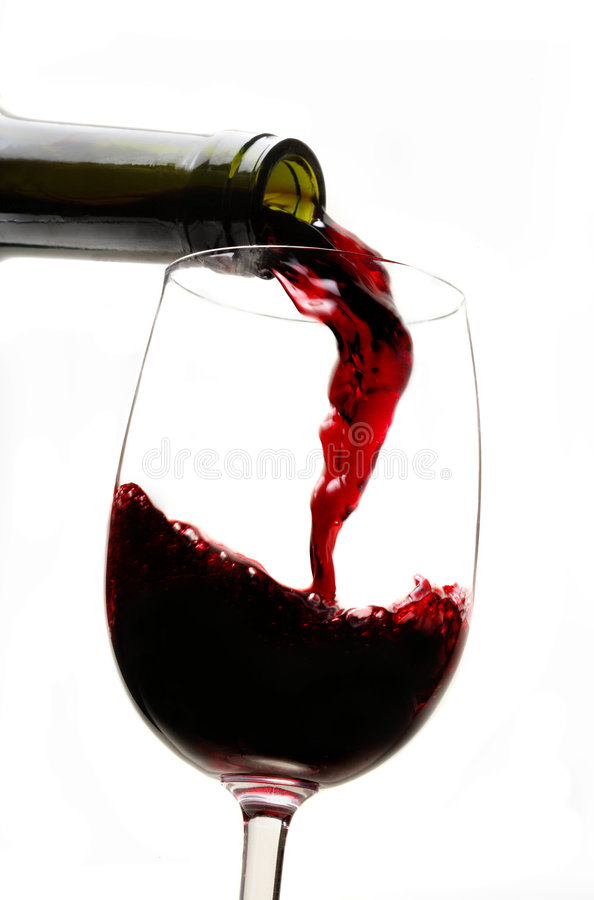 Vino rojo que vierte en el vidrio de vino fotos de archivo