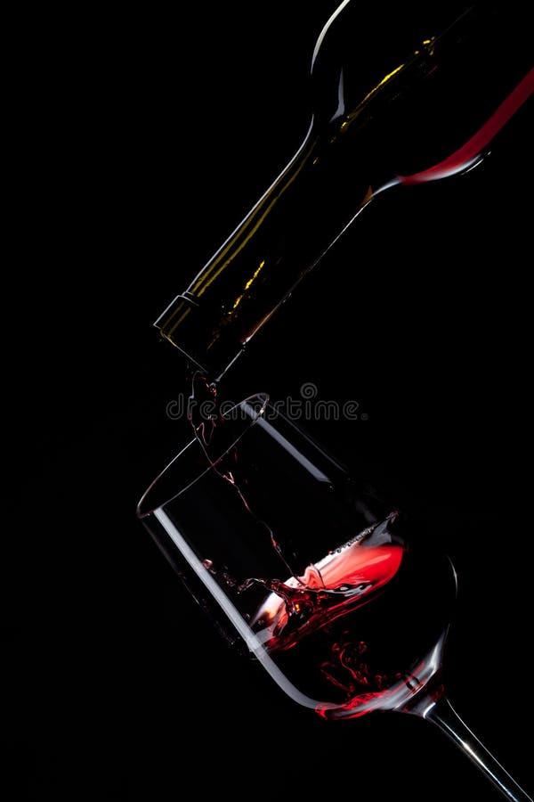 Vino rojo que vierte en el vidrio de vino en negro fotos de archivo libres de regalías