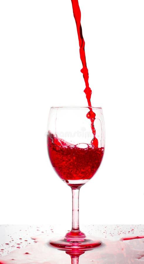 Vino rojo que vierte en un vidrio en el fondo blanco fotos de archivo libres de regalías
