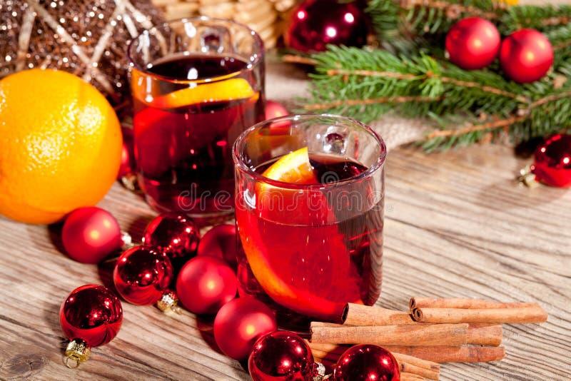 Vino rojo reflexionado sobre picante sabroso caliente con la Navidad de la naranja y del canela imagen de archivo libre de regalías
