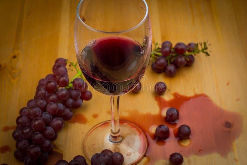 Vino rojo vertido en la copa de vino y derramado en la tabla de madera con las uvas frescas como diseño del fondo imagen de archivo