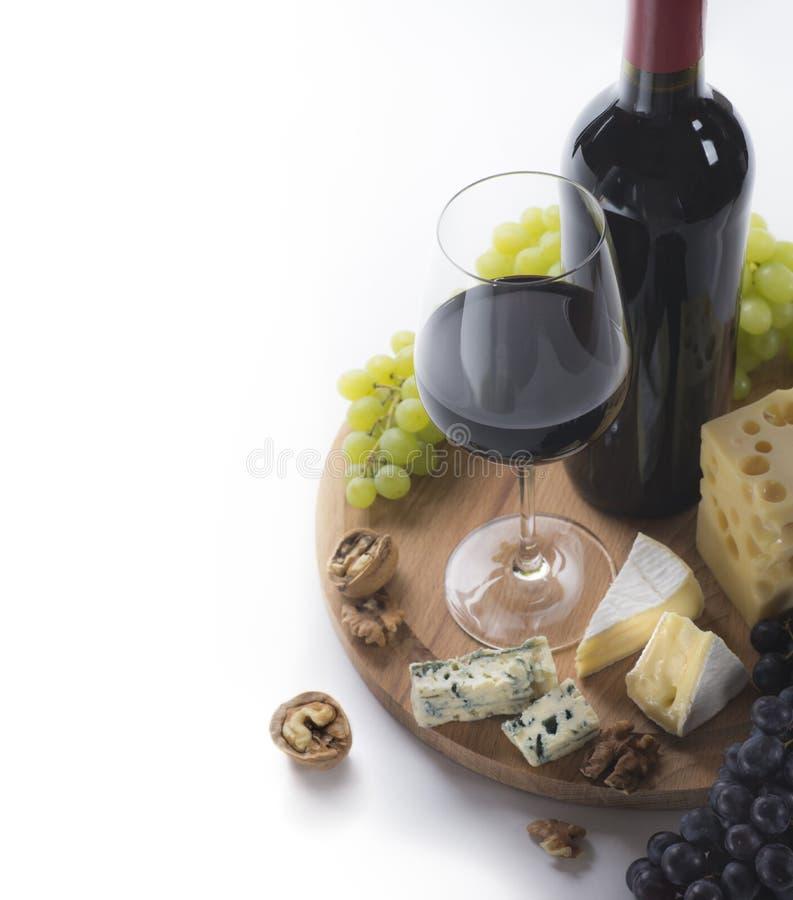 Vino rojo, vidrio, uvas, queso y nueces fotografía de archivo libre de regalías
