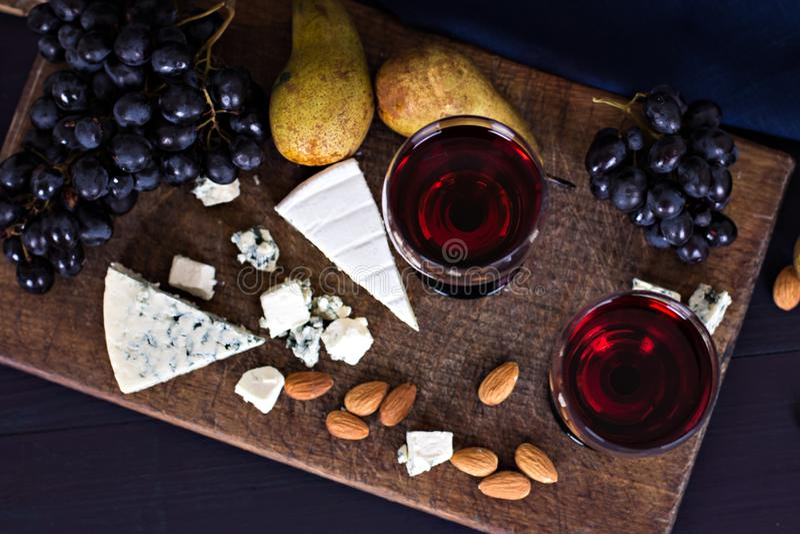 Vino rojo y bocados Vino, uvas, queso, nueces, aceitunas Tarde romántica, aún vida imágenes de archivo libres de regalías