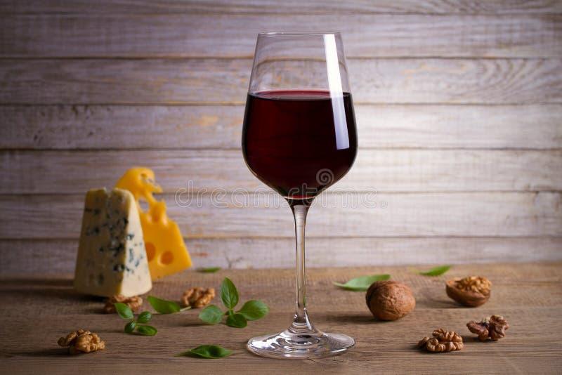 Vino rojo y queso en fondo de madera de la tabla Selección del aperitivo del queso o sistema del bocado del vino imagen de archivo