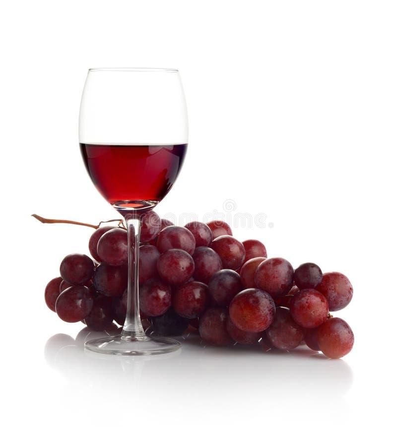 Vino rojo y uvas en blanco imagen de archivo libre de regalías
