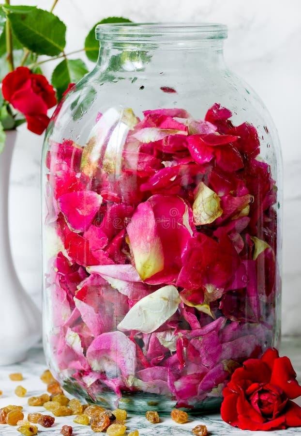 Vino rosato casalingo, petali rosa del tè in una bottiglia di vetro con il raisi fotografia stock libera da diritti