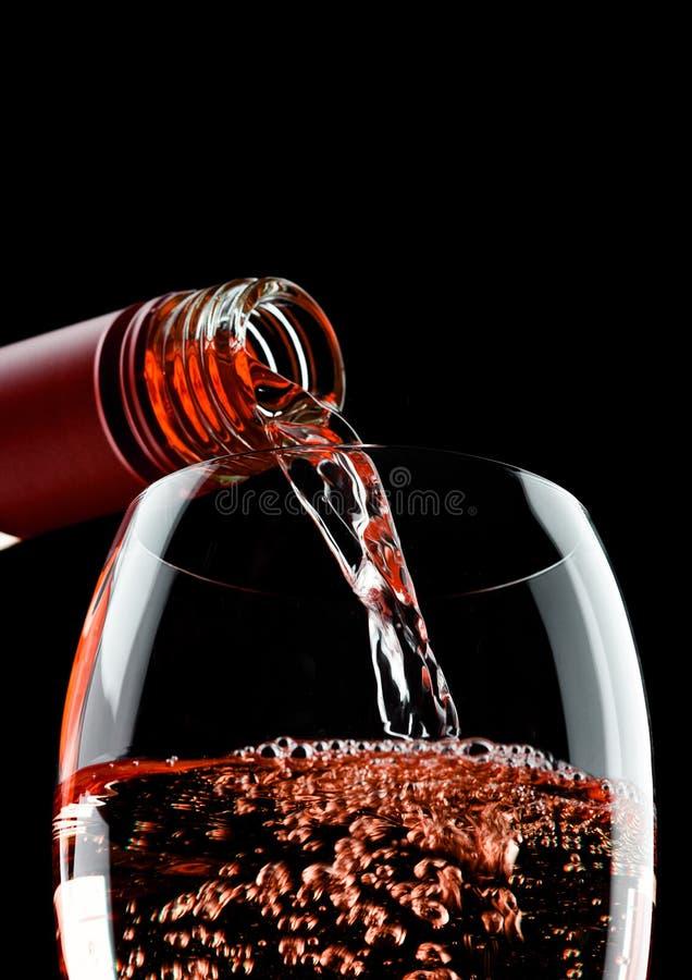 Vino rosato di versamento dalla bottiglia a vetro sul nero fotografia stock