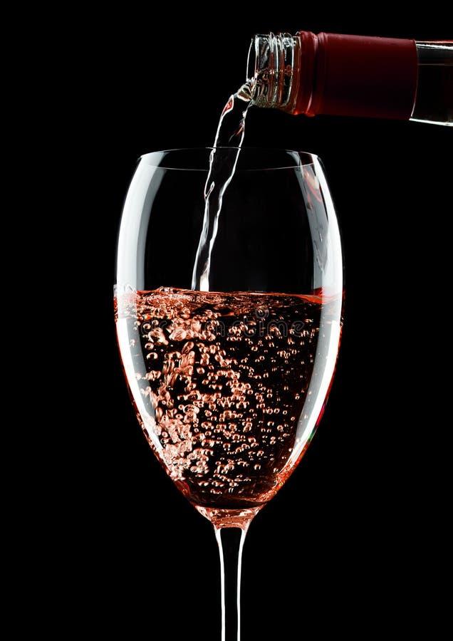 Vino rosato di versamento dalla bottiglia a vetro sul nero immagini stock