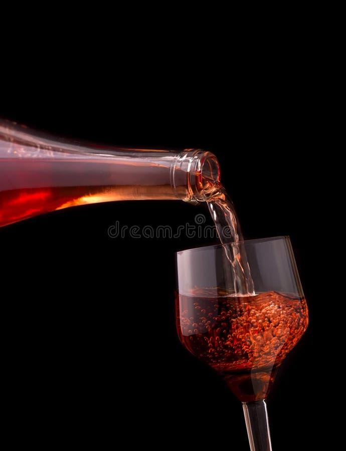 Vino rosato di versamento isolato su buio immagine stock libera da diritti