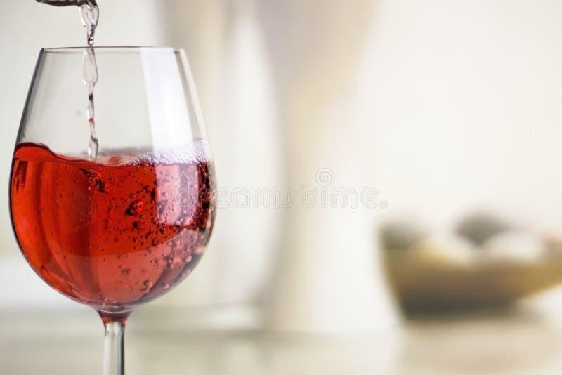 Vino rosato di versamento in un vetro di vino immagini stock libere da diritti