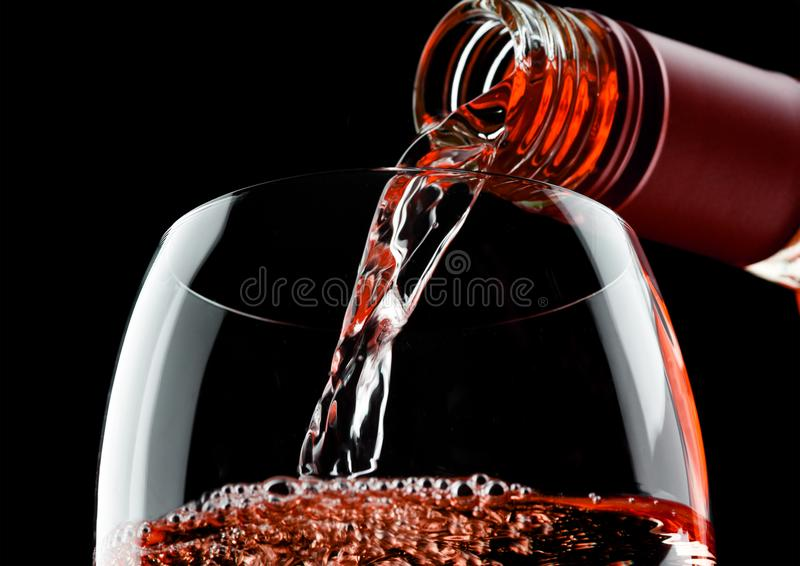 Vino rosato rosa di versamento dalla bottiglia a vetro sul nero fotografia stock libera da diritti