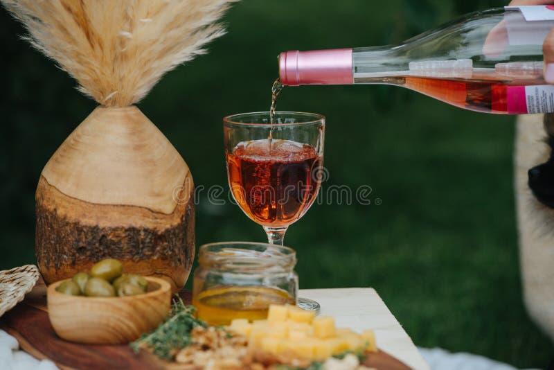 Vino rosato, versante dalla bottiglia nel vetro finché non sia pieno fotografia stock