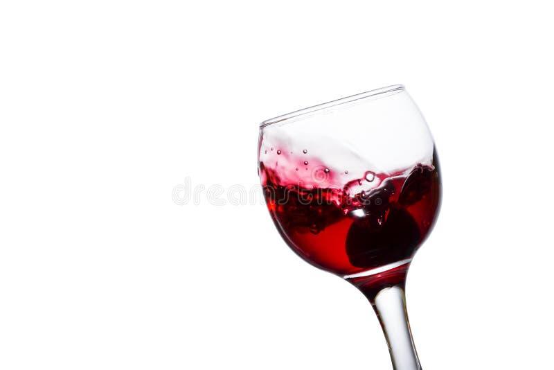 Vino rosso appetitoso che spruzza in un vetro con l'uva fotografie stock libere da diritti